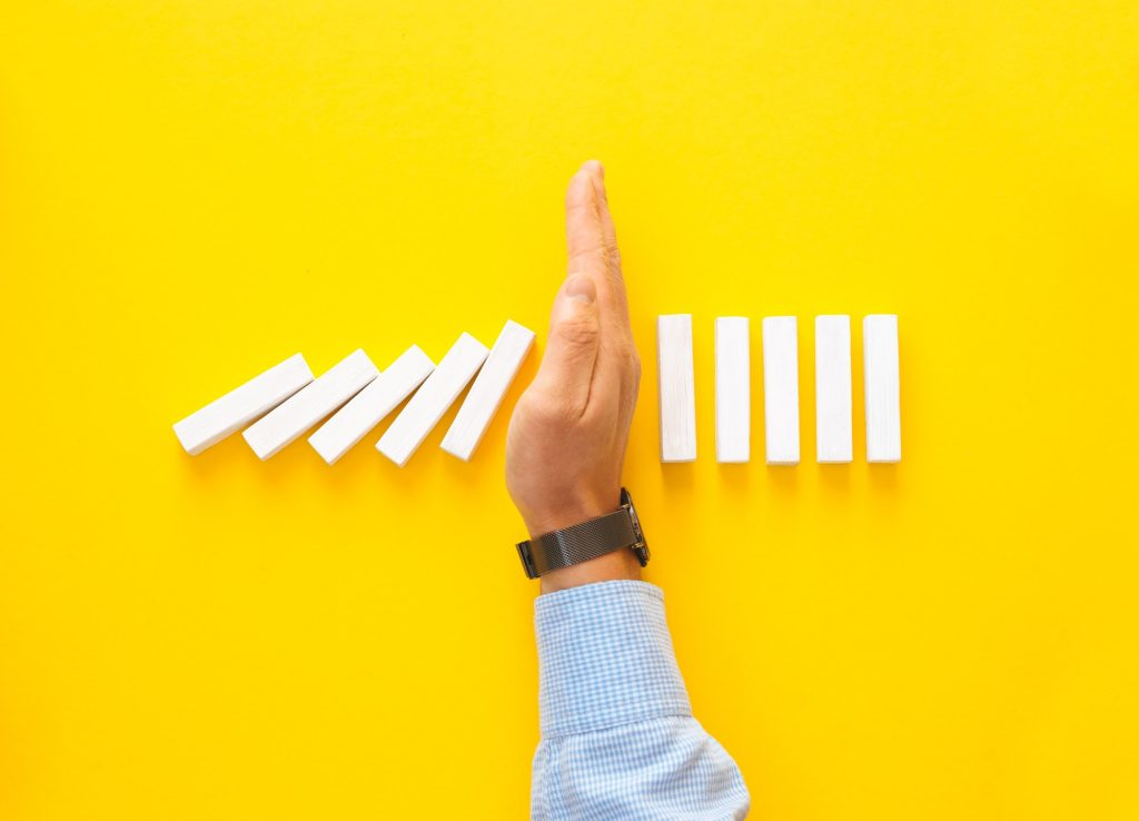 Businessman hand stopping falling dominos on yellow background. Business management crisis concept.