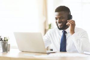 Happy consultant with headset looking at laptop