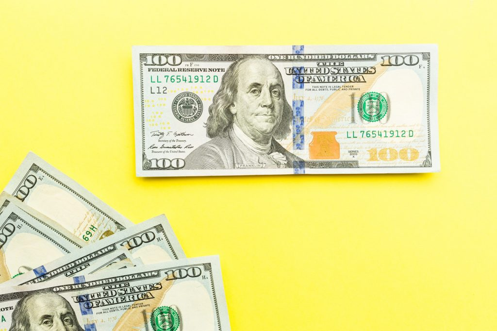 One hundred dollars bill lying on yellow background