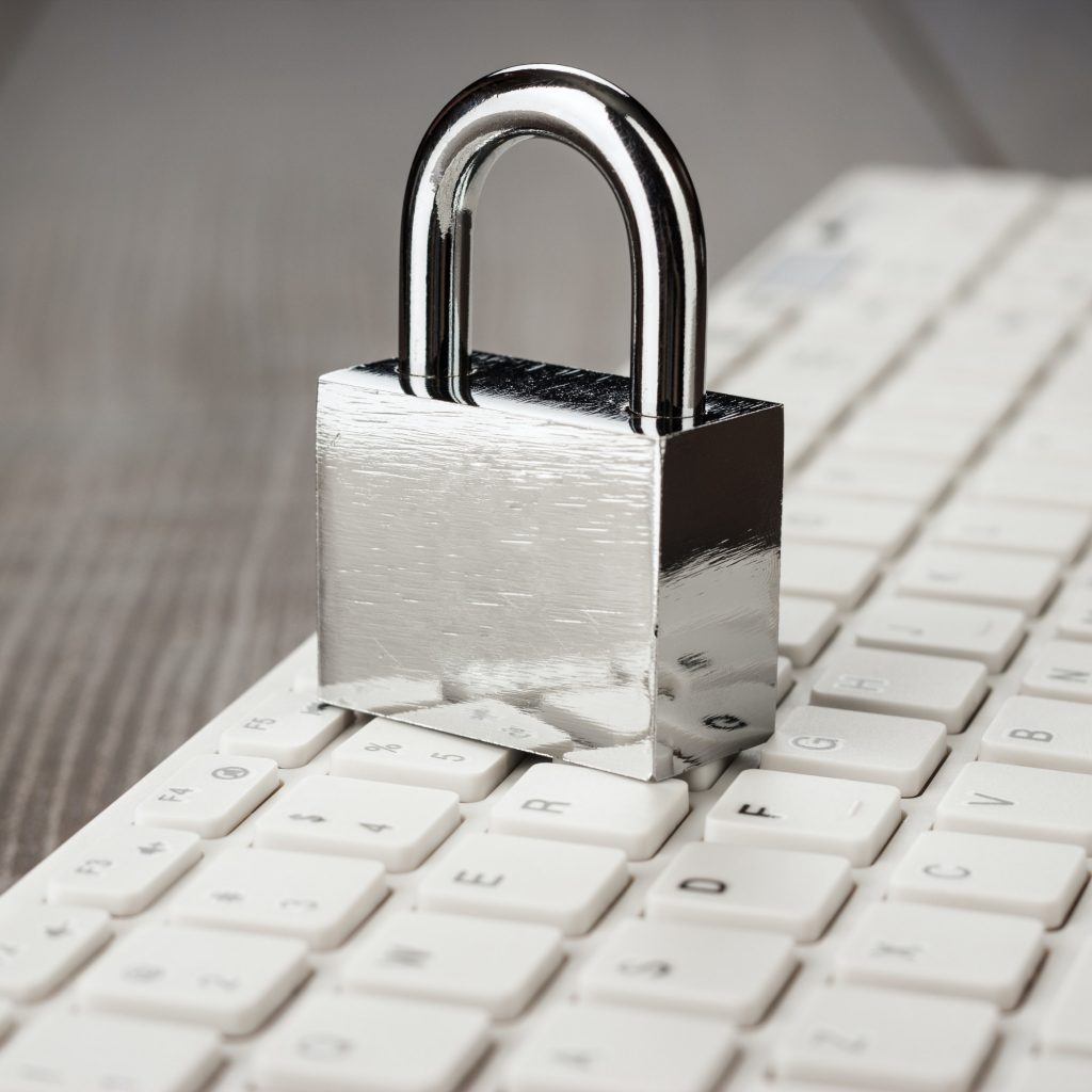 Padlock And White Computer Keyboard On The Wooden Office Table
