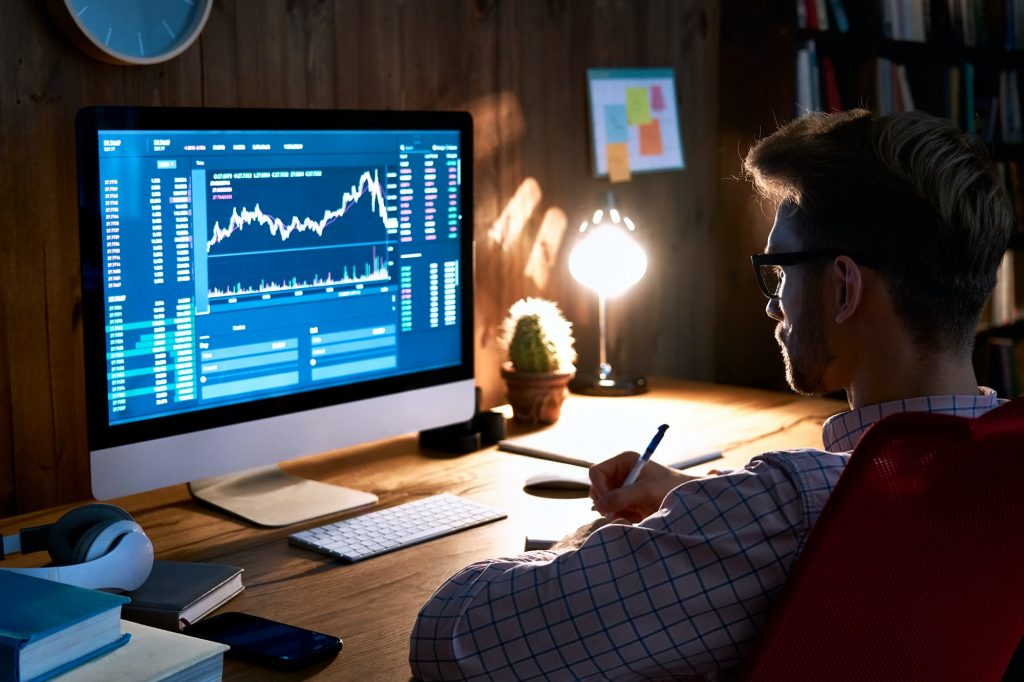 Stock market analyst looking at computer trading online analyzing data.